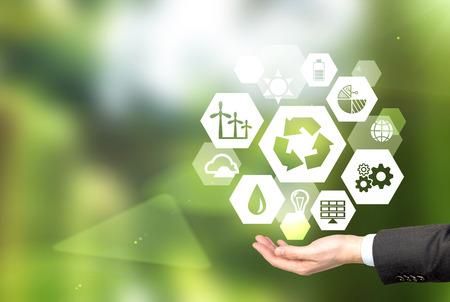 mão segurando sinais de diferentes fontes verdes de energia em forma de hexaedro, um sinal de 'reduzir, reutilizar, reciclar' no centro. Fundo verde borrado. Conceito de ambiente limpo.