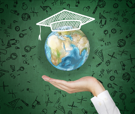 peak hat: A hand holding a painted Earth with an academic hat on it, different scentific signs around. Green background. Concept of studying Earth. Stock Photo