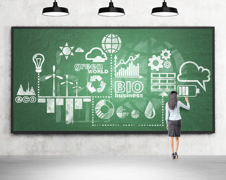 woman standing back: woman standing in front of a green blackboard and drawing a scheme of clean energy production. Three lamps above. Back view. Concrete background. Concept of clean energy.
