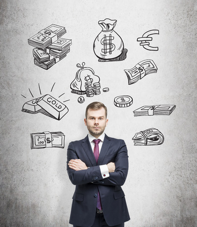 young man with arms crossed standing and looking in front, black pictures symbolizing money over his head. Concrete background. Front view. Concept of running into money.