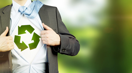 undone: man in a suit with a tie on his shoulder and shirt undone, a green sign of recyclable energy on a white background under it. No face. Concept of eco-friendly consumption. Stock Photo
