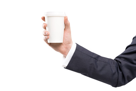 anecdote: A hand in a black suit holding a paper cup. White background. Concept of coffee break.
