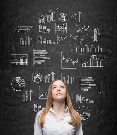 pizarron: Una mujer de negocios bastante mirando hacia arriba y de pie delante de una pizarra con muchos gr�ficos diferentes trazados en el mismo. Vista frontal. Concepto de presentar los datos en gr�ficos.