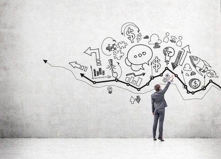 managing money: A young businessman drawing many different business icons on a concrete wall over a graph. Back view. Concept of business development.