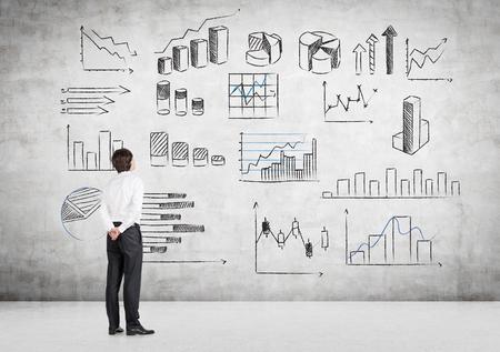 그것으로 그려 많은 다른 그래프와 함께 콘크리트 벽의 앞에 다시 서 손으로 젊은 사업가. 측면보기. 그래프에 데이터를 제시하는 개념.