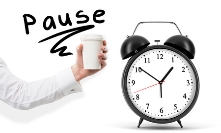 anecdote: A hand holding a paper cup, the word pause written over it. Black alarm clock to the right. White background. Concept of coffee break.