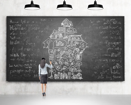 spending money: Woman standing in front of a blackboard and drawing different words and icons depicting opportunities provided by money arranged in an arrow. Back view. Concept of spending money