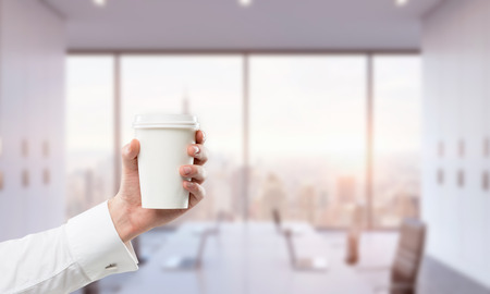 anecdote: A hand holding a paper cup. Blurred office at the background. Concept of coffee break.