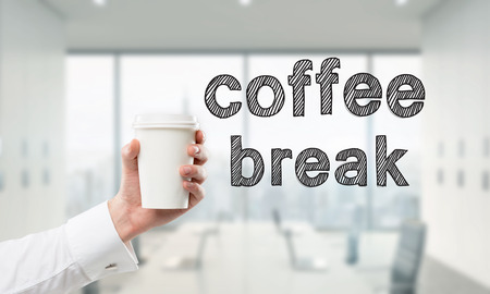 anecdote: A hand holding a paper cup. Coffee break written to the right. Blurred office at the background. Concept of coffee break.