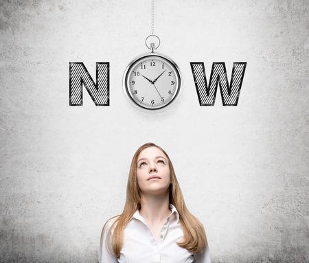 유행: 젊은 여자가 존재하는 기회와 시간에 대해 생각을 찾고. 포켓 시계와 그녀의 머리 위에 '지금'단어. 콘크리트 배경입니다. 전면보기. 현재 순 스톡 콘텐츠