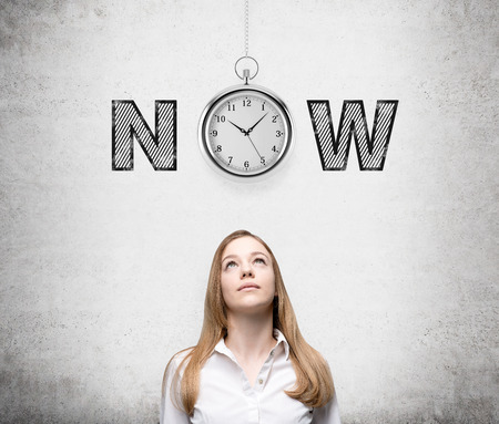 A young woman looking up thinking about present opportunities and time. A pocket watch and the word 'now' over her head. Concrete background. Front view. Concept of present moment.