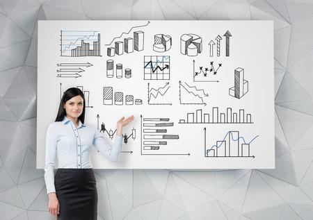 그것을 포위하는 많은 다른 그래프와 함께 흰색 포스터에서 가리키는 젊은 예쁜 사업가. 전면보기. 그래프에 데이터를 제시하는 개념.