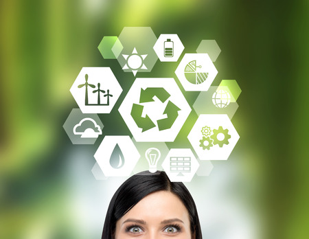 A big reduce, reuse, recycle sign over a womans head. Front view, only eyes seen. Blurred green background. Concept of clean energy. Stock Photo