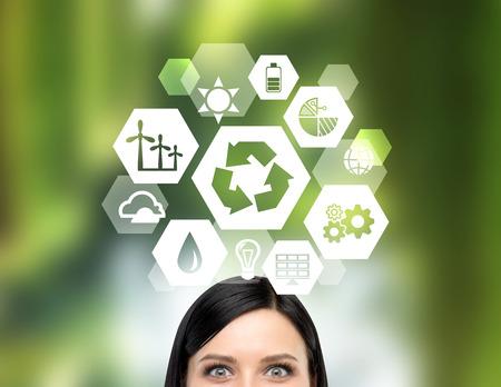 """Un gran """"reducir, reutilizar, reciclar"""" signo sobre la cabeza de una mujer. Vista frontal, sólo los ojos se ve. fondo verde borrosa. Concepto de energía limpia."""