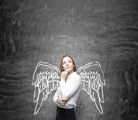snob: A young pretty woman with hand to the chin and eyes up standing in front of a blackboard with angel wings painted on it as if they were hers. Concept of lending wings.