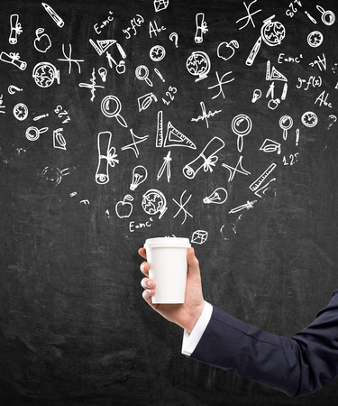 anecdote: A hand in a black suit holding a paper cup. Black background with different scientific symbols drawn over the cup. Concept of coffee break.