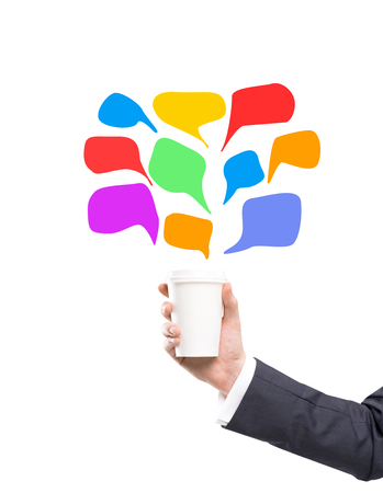 anecdote: A hand in a black suit holding a paper cup. Coloured clouds for remarks painted over it. White background. Concept of coffee break. Stock Photo
