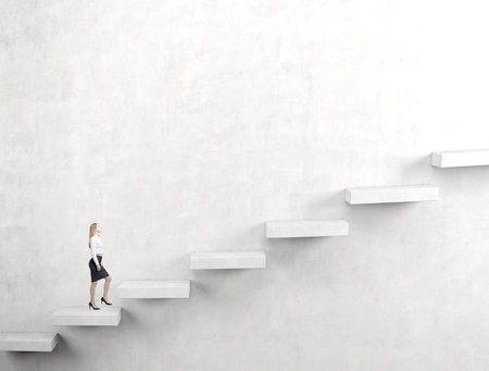steadily: A young woman going upstairs steadily. Concrete mackground. Concept of career growth.