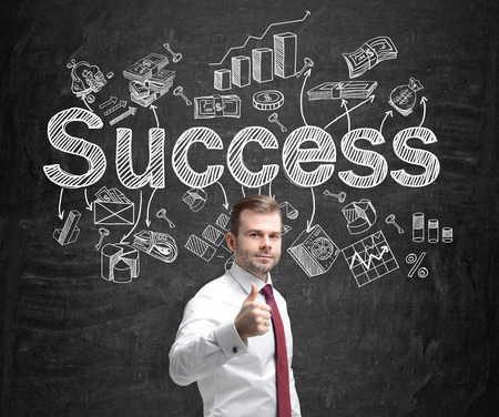 A young man holding a thumb up and standing in front of a blackboard with many different business icons and the word 'success' drawn on it. Concept of successful business development.