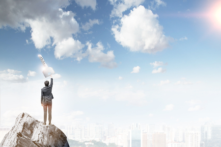 way out: A man standing on a cliff trying to reach a key-shape cloud. A city and blue sky at the background. Back view. Concept of finding a solution. Stock Photo
