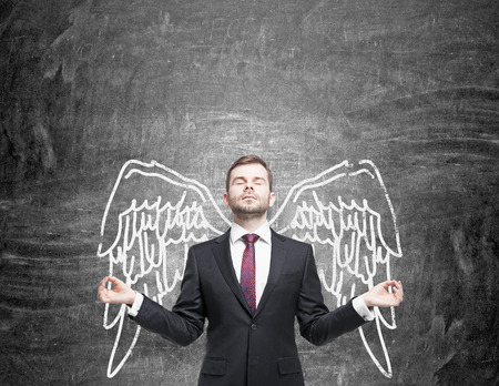 snob: A young man standing in a posture of meditation in front of a blackboard with angel wings painted on it as if they were his. Front view. Concept of lending wings.
