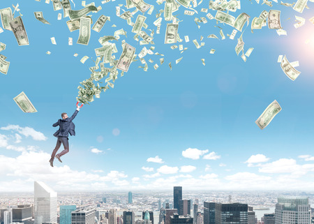 A young businessman flying over Paris with a magnet in hand that is pulled to money tornado. Paris and blue sky at the background. Concept of strivig for wealth.