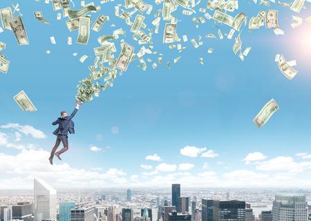 Un joven empresario volando sobre París con un imán en la mano que se tira al tornado dinero. París y el cielo azul en el fondo. Strivig concepto de la riqueza.