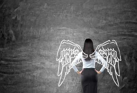 A young woman standing in front of a blackboard with angel wings painted on it as if they were hers, right-centered. Back view. Concept of lending wings.