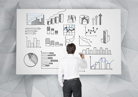 young businessman drawing many different graphs on a white poster. Back view. Grey geometric background. Concept of presenting data in graphs.