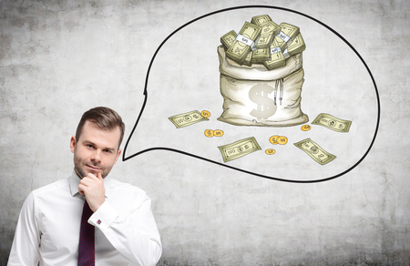 money packs: A young man with his hand to the chin thinking about money. A picture of a bag of money to the right. Front view. Concrete background. Concept of having a lot of money. Stock Photo
