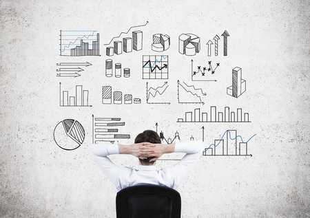 managing money: A businessman with hands on the back of his head sitting in an armchair in front of a concrete wall with many different graphs drawn on it. Back view. Concept of presenting data in graphs. Stock Photo