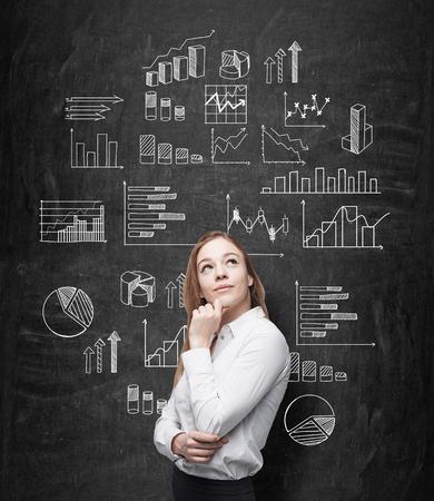찾고있는 턱 손으로 젊은 꽤 사업가 그것에 그려진 많은 다른 그래프와 함께 칠판 앞에 서있다. 그래프에 데이터를 제시하는 개념.