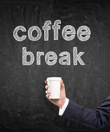 anecdote: A hand in a black suit holding a paper cup. Coffee break written over it. Black background. Concept of coffee break.