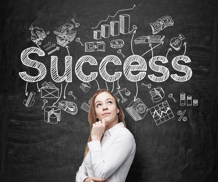 A young woman with hand to the chin looking up and standing in front of a blackboard with many different business icons and the word 'success' drawn on it. Concept of successful business development.