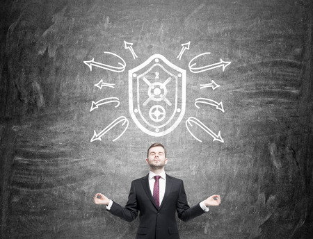 rebounding: A man in the posture of meditation with eyes closed standing under a shield drawn on the blackboard, arrows around the shield as if rebounding from it. Front view. Concept of security.