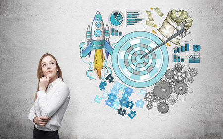 set goal: A woman looking up, a picture of a target surrounded by pictures of money, rocket, charts, cogwheels and puzzles painted to the right. Concrete background. Concept of achieving a set goal. Stock Photo