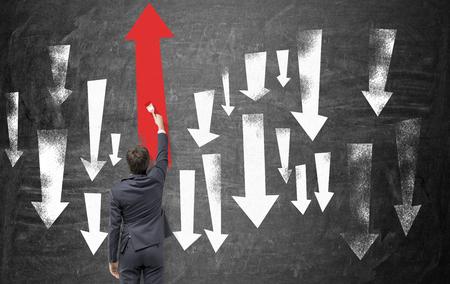 Un hombre de negocios que pinta grandes flechas arriba y abajo en la pizarra, el mayor de ellos es una roja para arriba. Vista trasera. Concepto de moverse hacia arriba. Foto de archivo - 51986023