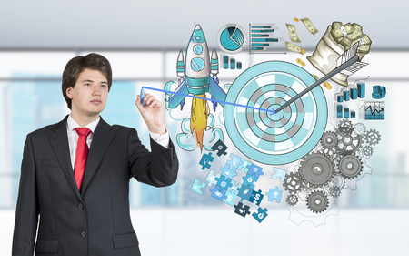 achieving: A man drawing a picture of a target surrounded by pictures of money, rocket, charts, cogwheels and puzzles between hands. Blurred office background. Front view. Concept of achieving a set goal.