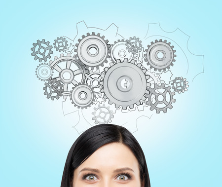 unachievable: A young woman thinking about a watch mechanism, a picture of cogwheels over her head. Front view, only eyes seen. Blue background. Concept of creating a mechanism. Stock Photo