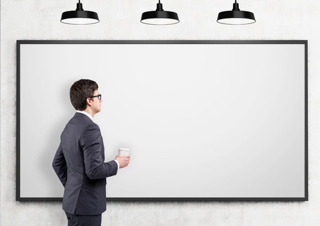 rasa: A businessman with a paper cup looking at a blank poster on a concrete wall, three lamps above. Side view. Concrete background. Concept of drawing.