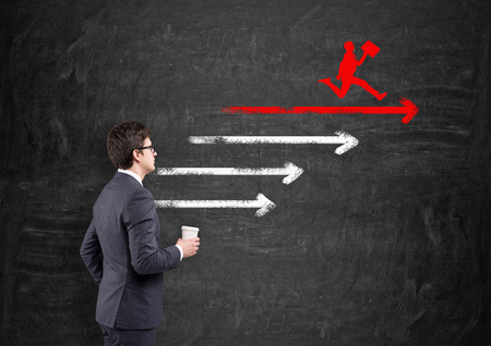 cup four: Young businessmanwith a paper cup standing in front of four horizontal arrows and a red silhouette of a running man with a folder on the top one drawn on the blackboard. Concept of setting a goal.