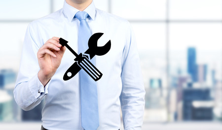car service: A man in a shirt touching an image of a screwdriver and a wrench crossed in front of him. Front view, no face. Blurred office at the background. Concept of fixing things. Stock Photo