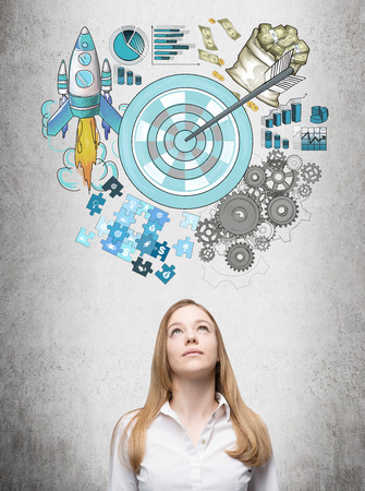 achieving: A woman looking up, a picture of a target surrounded by pictures of money, rocket, charts, cogwheels and puzzles painted over her head. Concrete background. Concept of achieving a set goal.