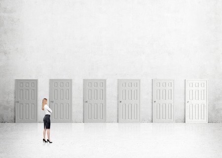 out of doors: A young businesswoman with hands crossed standing in a room with numerous closed doors. Side view. Concrete background. Concept of finding a way out.