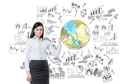 A young beautiful woman pointing at the Earth drawn in colour surrounded by different graphs and diagrams. Front view. White background. Concept of thinking about the planet.