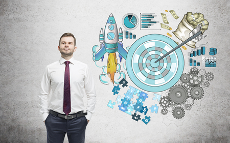 achieving: A man with hands in pockets, a picture of a target surrounded by pictures of money, rocket, charts, cogwheels and puzzles painted to the right. Concrete background. Concept of achieving a set goal.