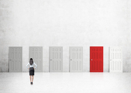 way out: A young businesswoman with hands on hips standing in a room with numerous closed doors, one of them red. Back view. Concrete background. Concept of finding a way out.