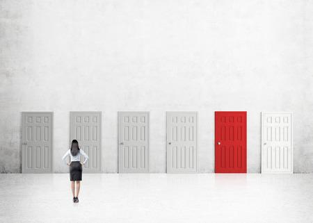conclusion: Una mujer de negocios con las manos en las caderas de pie en una habitación con numerosas puertas cerradas, uno de ellos de color rojo. Vista trasera. Fondo concreto. Concepto de encontrar una salida. Foto de archivo