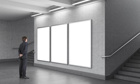 A man standing in front of three blank vertical billboards in the underground, stairs up on both sides. Grey walls. Concept of underground advertising. Stock Photo