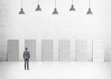 way out: A young businessman with hands in pockets standing in a room with numerous closed doors. Five lamps above. Back view. Concrete background. Concept of finding a way out. Stock Photo